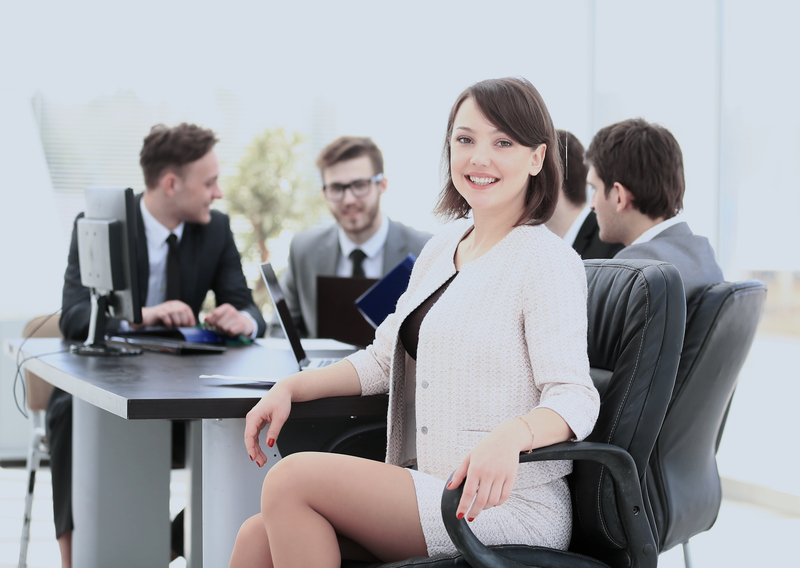 successful female accountant smiling while sitting at a table with other accountants