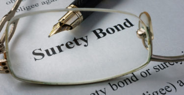 eye glasses laying on top of surety bond document with pen
